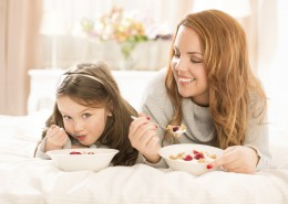 Mother and daughter eating on bed.