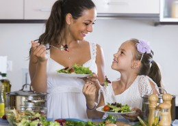 happy russian family of two having healthy lunch with veggies at home