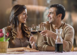 Smiling couple enjoying in winery and toasting with red wine.